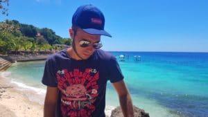 homme-casquette-plage-eau turquoise