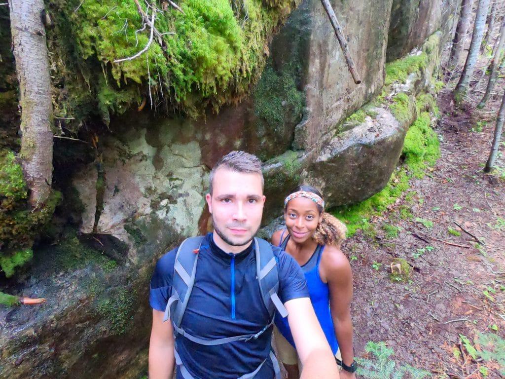 selfie de maeva et anthony du blog de voyage prtir loin devant un rocher de la forêt de la randonnée du mont Menaud