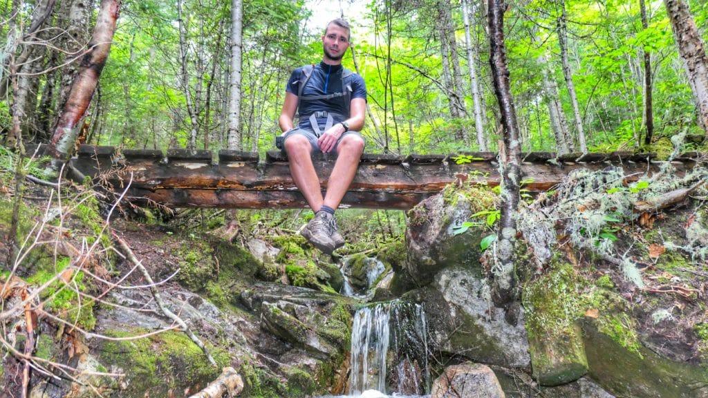 Anthony de Partir Loin assied sur un petit pont au dessus d'un petite chute d'eau dans la forêt des Morios