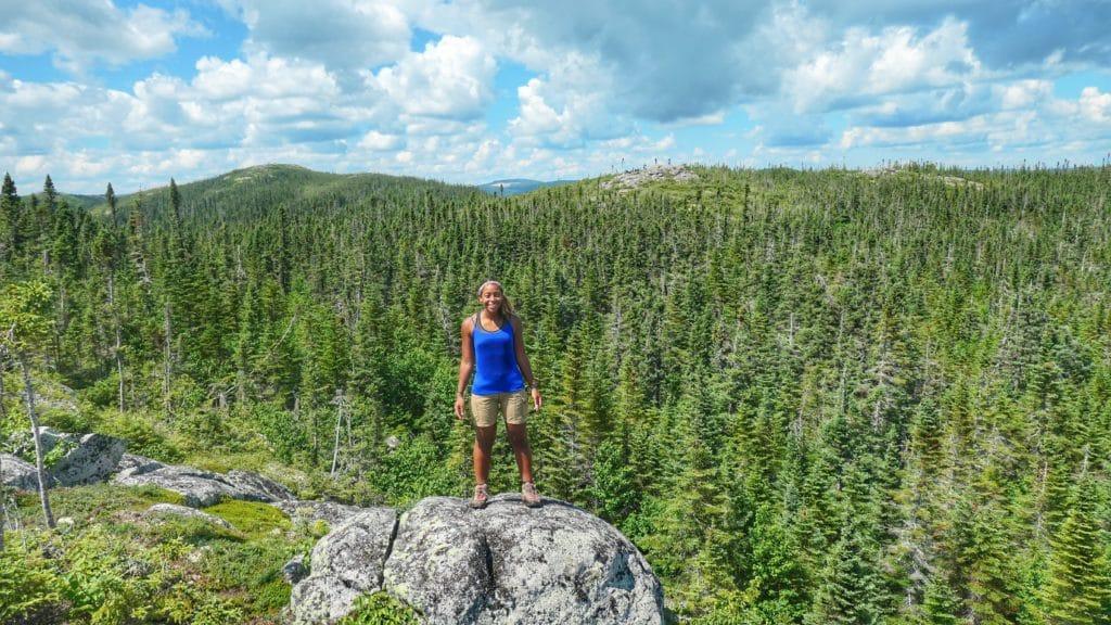 Maeva du blog de Partir Loin debout sur une roche avec une forêt dense derrière elle