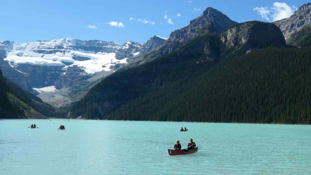 vue sur le lac louise avec les montagnes en arrière plan et les petits canoé sur le lac