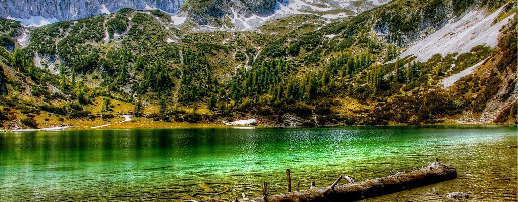 Lac bleu azure avec en arrière plan une vue sur les montagnes enneigées