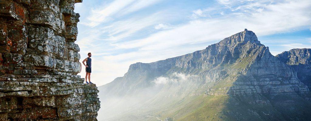 homme sur une montagne face à une vue surprenante